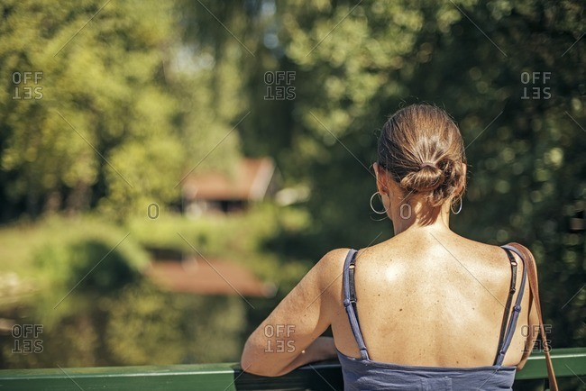 Woman standing on bridge looking out at river in the Netherlands