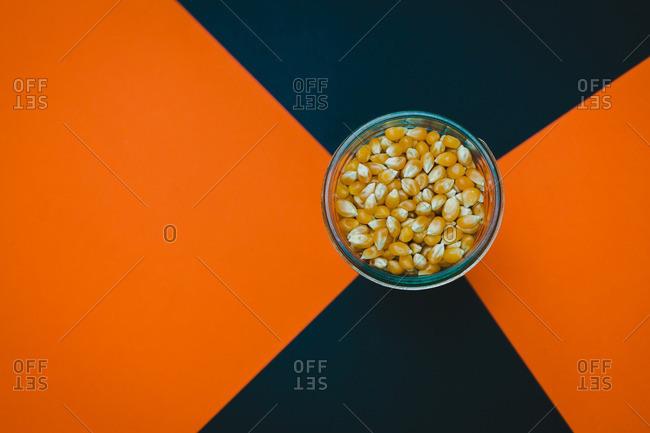 Bowl of corn kernels on a black and orange background