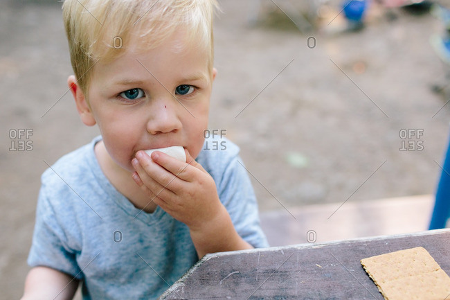 Toddler boy eating a marshmallow while waiting to make s'mores