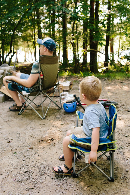 Father and son sitting in folding camp chairs at family campsite