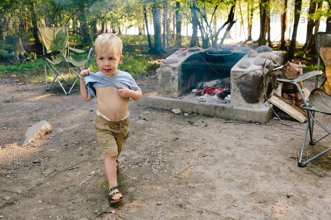 Little boy lifting up his shirt while walking in front of an outdoor fireplace at a campground