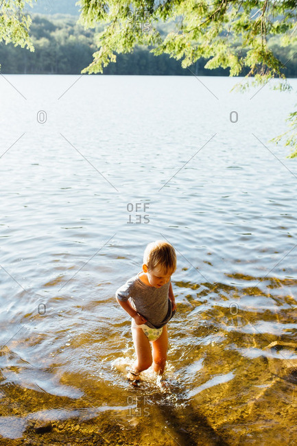 Toddler boy wading in the water at the lakeshore