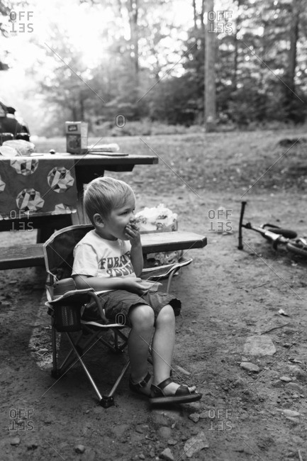 Toddler boy eating lunch while sitting in front of a picnic table at a campsite
