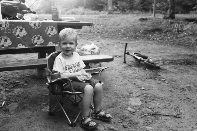Toddler boy sitting in a folding camp chair in front of a picnic table