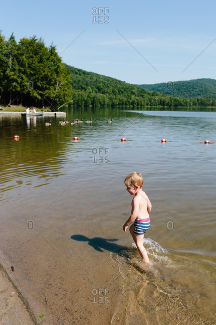 Toddler boy wading in the water near the shore of a lake