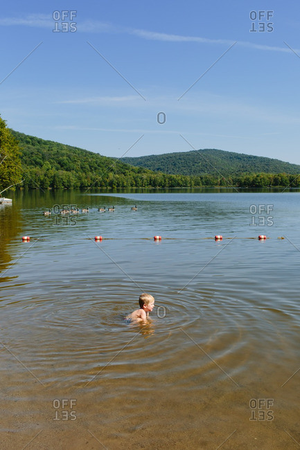 Little boy playing in the water near the shore of a lake
