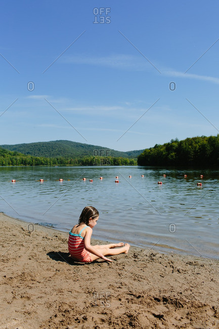 Girl sitting along the shore of a lake