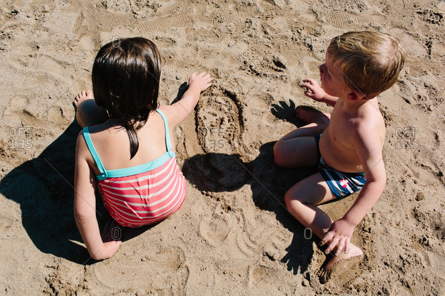 Brother and sister playing in the sand