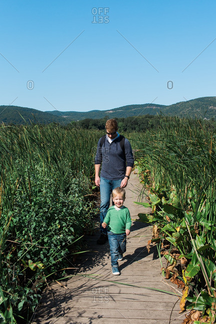 Father and son walking on a boardwalk through a natural area