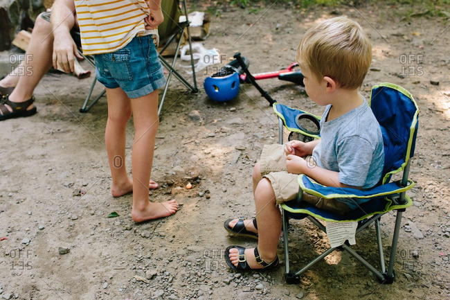 Toddler boy sitting in a folding camp chair at a family campsite