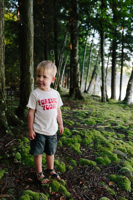 Toddler boy standing in a forested natural area