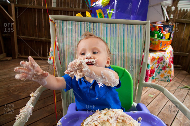 Young Caucasian boy celebrates his first birthday making a mess with Cake outside during Summer