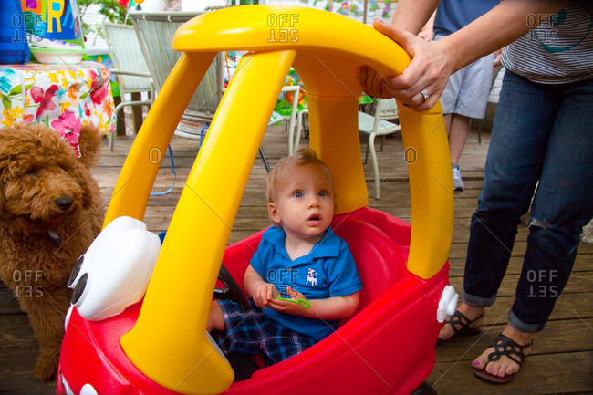 Young Caucasian boy celebrates first birthday with friends and family behind his house during Summer