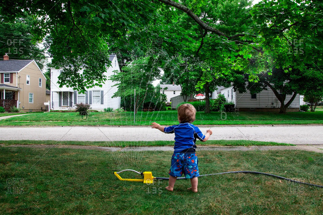 Caucasian Baby Boy plays with a water sprinkler in his front Lawn during Summer