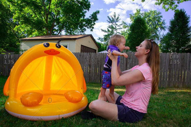 Caucasian Mother and Son play in and around their backyard inflatable pool