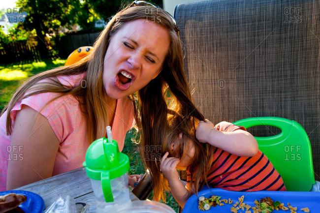 Caucasian Baby Boy pulls his Mothers hair while he eats food at a picnic Table in his Backyard