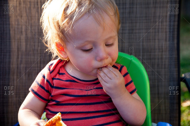 Caucasian baby boy sits in high chair and eats food at a picnic