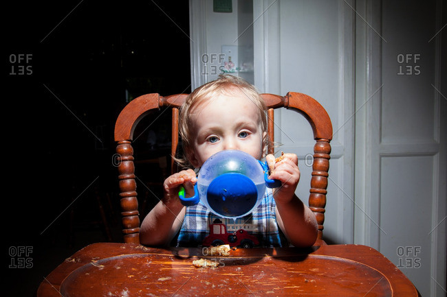 Baby Caucasian boy sitting in vintage wooden High Chair eating and drinking