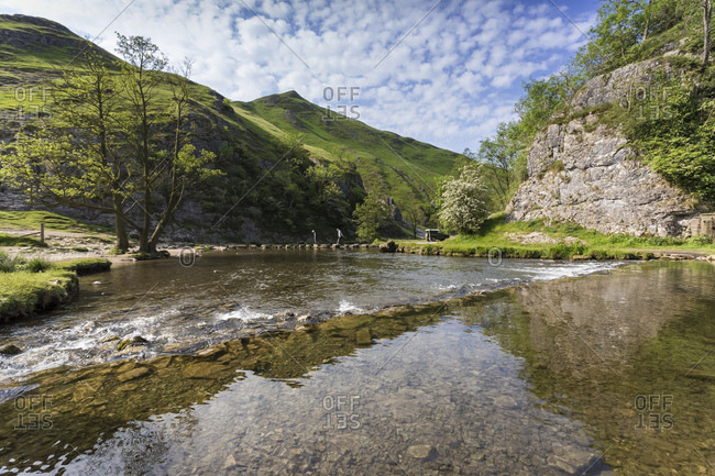 Dovedale reflections, hikers on stepping stones and Thorpe Cloud, limestone gorge in spring, Peak District, Derbyshire, England, United Kingdom, Europe