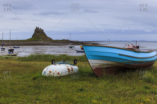 Fishing boats onshore and beach at low tide with Lindisfarne Castle and Farne Islands, Holy Island, Northumberland, England, United Kingdom, Europe
