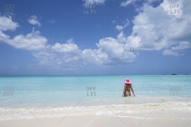 A bather with a pink hat in the turquoise waters of the Caribbean Sea, The Nest, Antigua, Antigua and Barbuda, Leeward Islands, West Indies, Caribbean, Central America