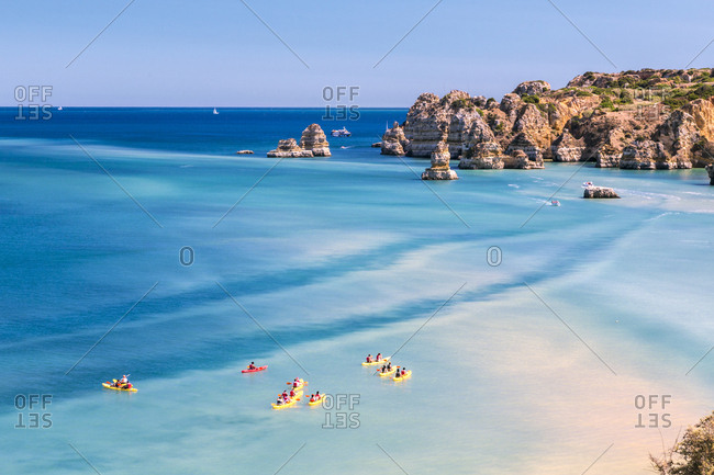 Canoes in the turquoise water of the Atlantic Ocean surrounding Praia Dona Ana beach, Lagos, Algarve, Portugal, Europe