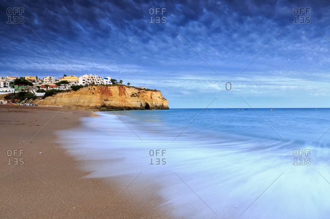 Ocean waves crashing on rocks and beach surrounding Carvoeiro village at sunset, Lagoa Municipality, Algarve, Portugal, Europe