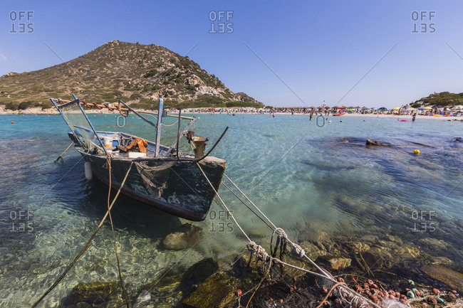 A fishing boat in the turquoise sea surrounding the sandy beach, Punta Molentis, Villasimius, Cagliari, Sardinia, Italy, Mediterranean, Europe
