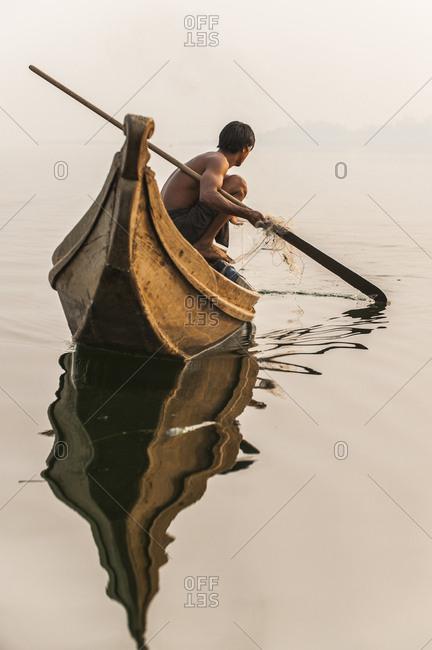 A fisherman pulls in his net on Indawgyi Lake in Kachin State, Myanmar (Burma), Asia
