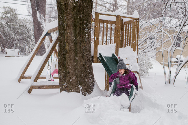Girl playing on a slide during a snowstorm