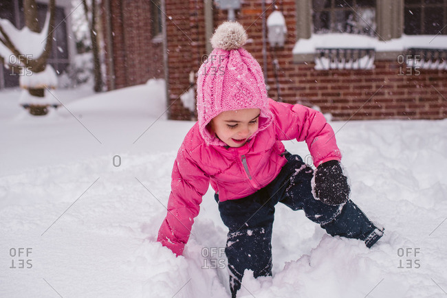 Girl playing in deep snow in her yard