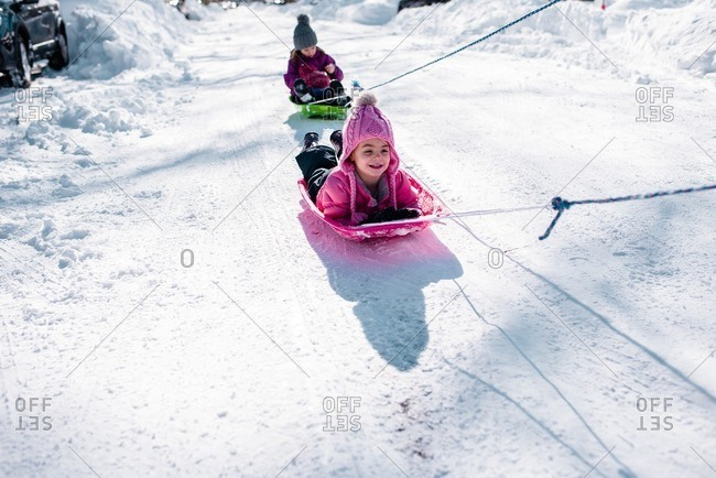 Children being pulled on sleds down a snow covered street