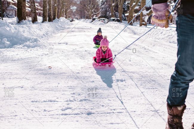 Children being pulled on sleds down a snowy street