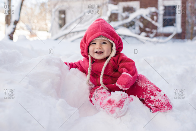Toddler wearing a snowsuit sitting on a pile of snow