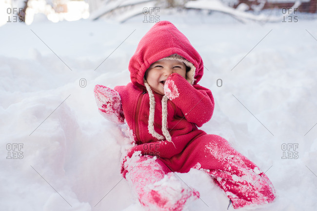 Toddler in a snowsuit sitting on a pile of snow