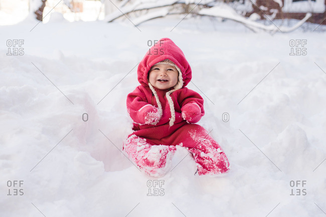 Toddler in a pink snowsuit sitting on a pile of snow