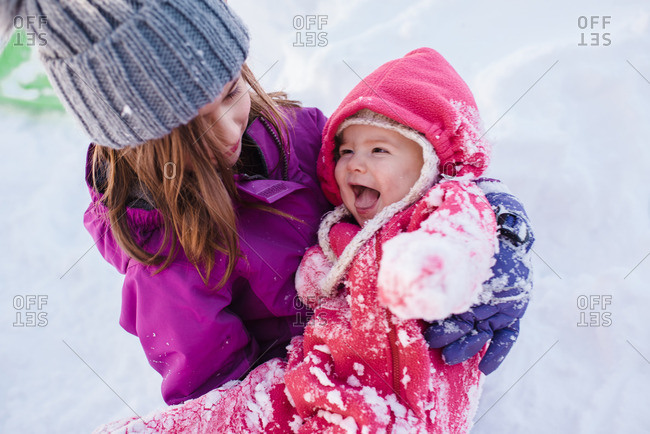 Two children playing outside together in the snow