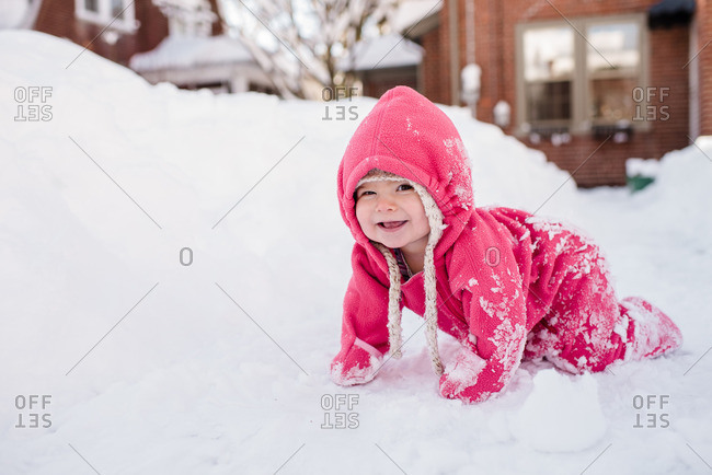 Toddler in a pink snowsuit crawling through the snow