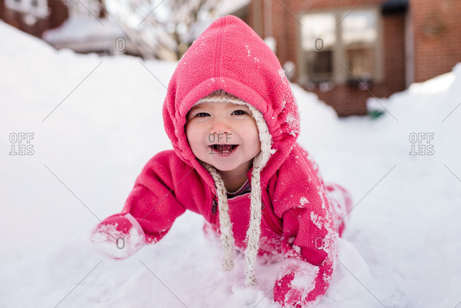 Toddler in a pink snowsuit crawling in the snow