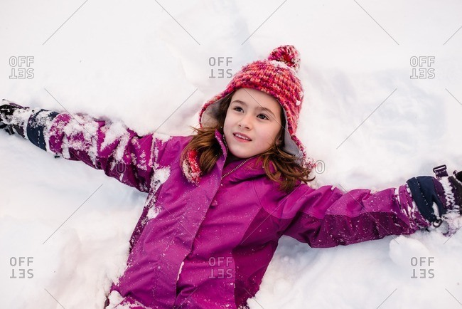 Girl lying down in the snow with her arms extended