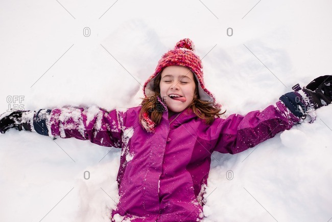 Girl lying down in the snow with her arms extended and her tongue out