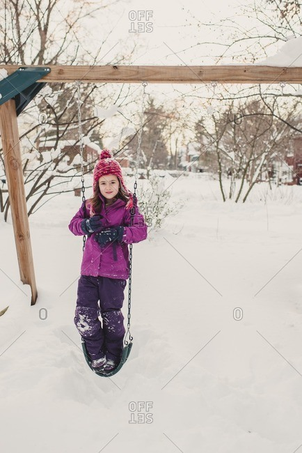 Girl standing on a swing on a snow covered playground