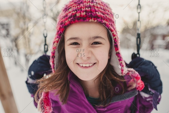 Close-up of a girl on a swing on a snow covered playground