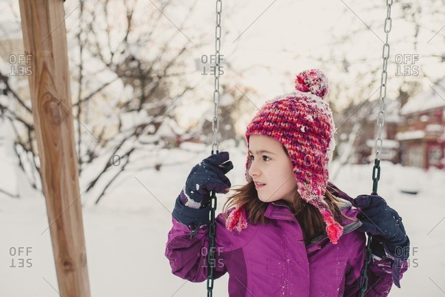 Girl on a swing on a snow covered playground