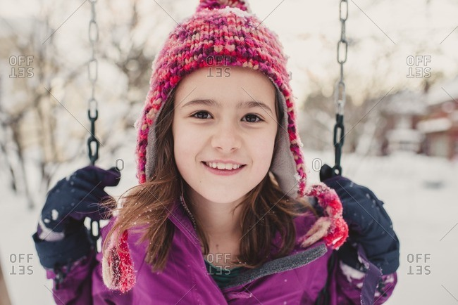 Portrait of a girl on a swing on a snow covered playground