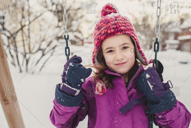 Portrait of a girl on a swing on a snowy playground