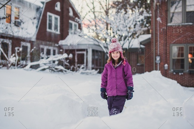 Portrait of a smiling girl standing in the snow in a suburban neighborhood