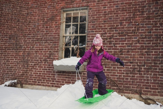 Girl standing on a sled on top of a snow drift next to a house