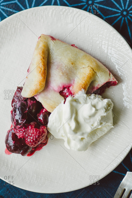 A piece of berry galette served with whipped cream