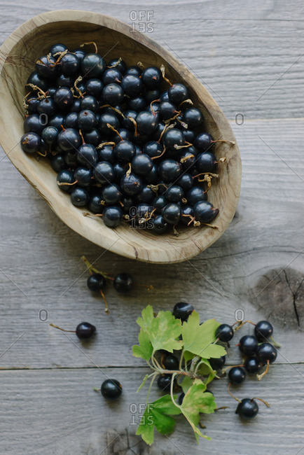 A wood bowl filled with black currants
